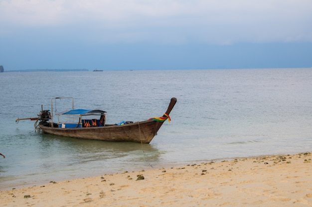 Longtail-boot am tropischen strand mit himmel abendsonnenlicht