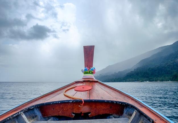 Longtail-holzboot, das im sturmblauen meer reist