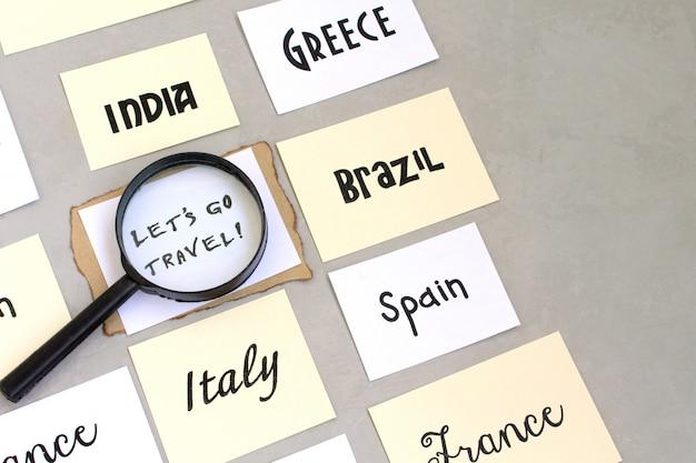 Los geht's mit reisetextwörtern, länderauswahl, kartenlupenkompass, grauer hintergrund
