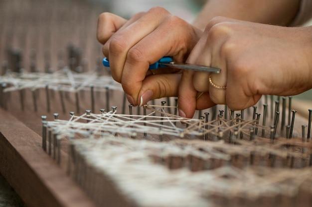 Loses ende mit nägeln an holzbrett gebunden, handgefertigtes textilkonzept