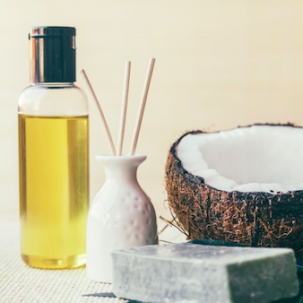 Lotion, kokosnuss und vase mit stöcken