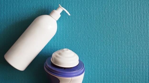 Lotion und anti-cellulite-massagegerät auf blauem hintergrund. gesundes und schönes hautkonzept.