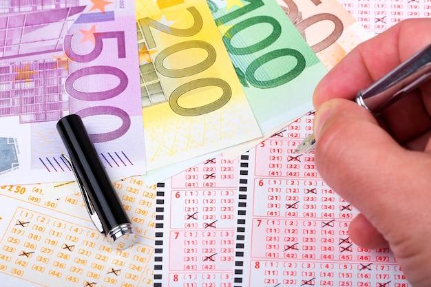 Lottoschein mit einem stift und europäischem geld