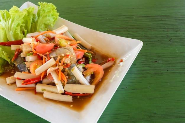 Lotus stem thai spicy salad auf einem grünen tisch, thailändisches lokales essen.