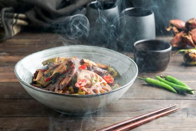 Lotuswurzel- oder rhizompfanne mit shiitake-pilzen, gewürzen, peperoni, dunkler sojasauce und frühlingszwiebeln
