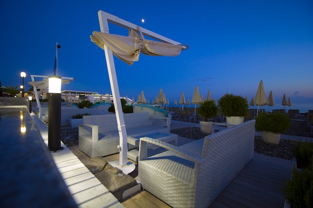 Lounge-bereich am strand sonnenschirme am abend bei sonnenuntergang