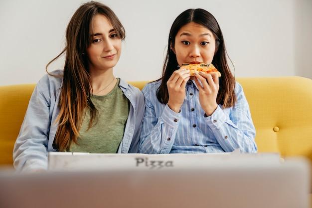 Lounging frauen, die pizza mit film essen