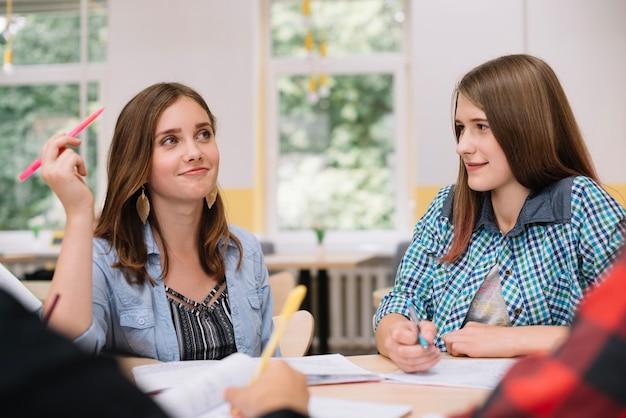 Lovely girls mit klassenkameraden am schreibtisch