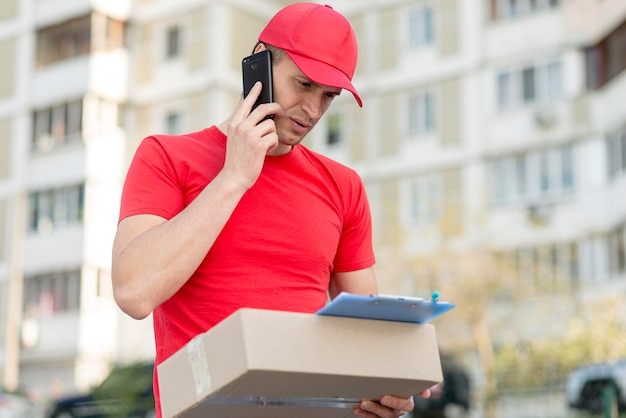 Low angle delivery guy mit telefon