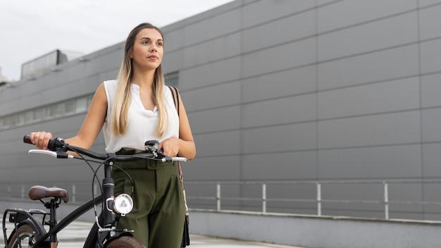 Low angle frau, die neben fahrrad geht