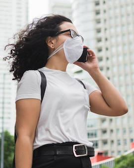 Low angle frau mit medizinischer maske, die am telefon spricht