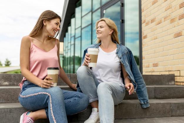 Low angle girls plaudern und trinken ihren kaffee