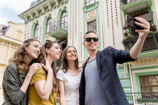 Low angle gruppe von freunden, die selfie nehmen