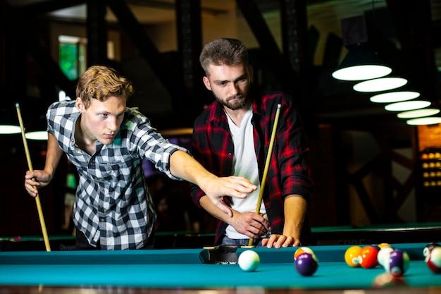 Low angle jungs mit pool queues spielen billard