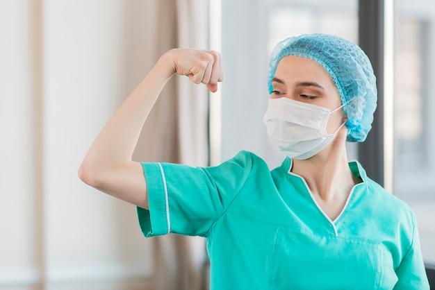 Low angle krankenschwester zeigt muskeln