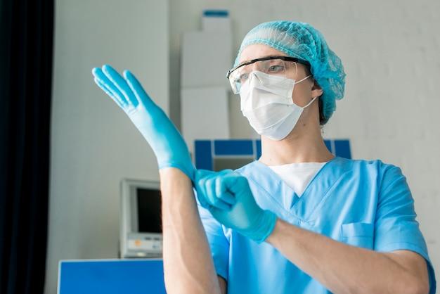 Low angle krankenschwester zieht handschuhe an