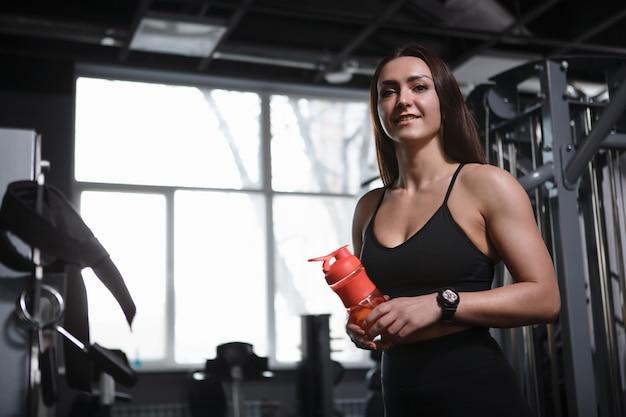 Low angle shot einer glücklichen schönen sportlerin, die in die kamera lächelt und sich nach dem training im fitnessstudio ausruht