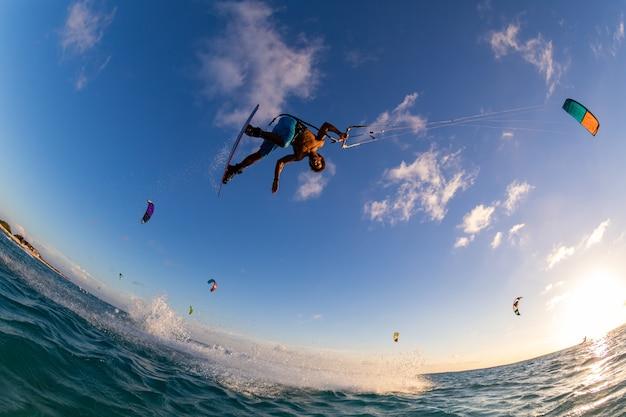 Low angle shot einer person, die gleichzeitig beim kitesurfen surft und einen fallschirm fliegt