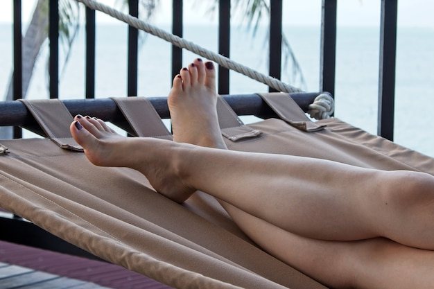 Low angle shot einer weißen frau, die sich am strand an einem heißen sommertag entspannt