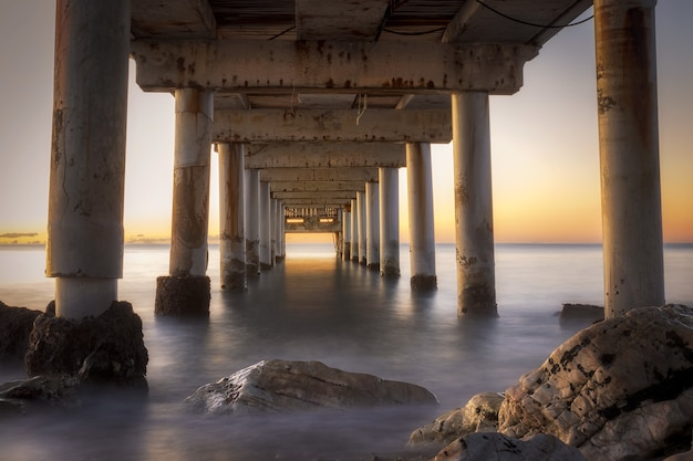 Low angle shot eines piers in marbella, spanien bei sonnenaufgang