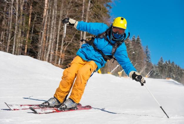 Low angle shot eines professionellen skifahrers beim skifahren auf der piste