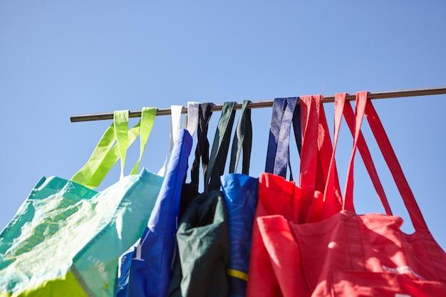 Low angle shot von bunten umweltfreundlichen wiederverwendbaren stoffbeuteln, die an einer stange hängen - kein plastikkonzept