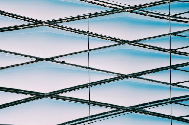 Low angle shot von geometrischen metallkabeln auf einem glasgebäude