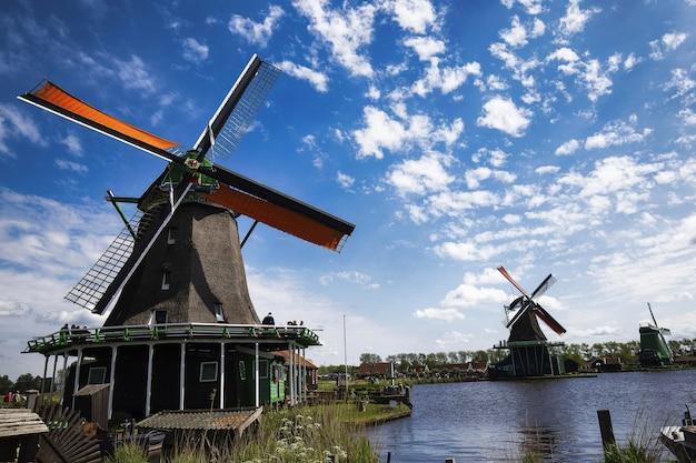 Low angle shot von windmühlen in zaanse schans nachbarschaft in der nähe des sees in den niederlanden