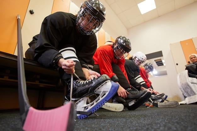 Low angle view bei weiblicher eishockeymannschaft, die ausrüstung anlegt