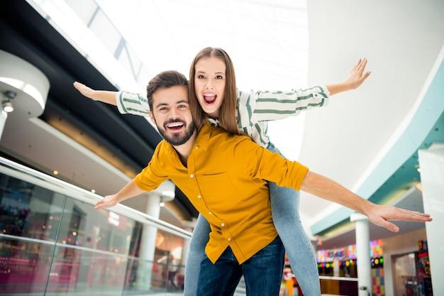 Low angle view foto einer lustigen dame, die arme wie flügel ausbreitet, ein hübscher kerl trägt ihr huckepack-freizeit-einkaufszentrum zusammen gute laune, die spaß hat, abenteuer zu treffen, lässiges outfit drinnen tragen