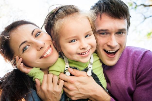 Low angle view portrait der glücklichen lächelnden familie im herbst. fokus auf frau