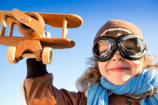 Low angle view portrait von lustigen kindern, die mit spielzeugflugzeug vor blauem himmelshintergrund spielen