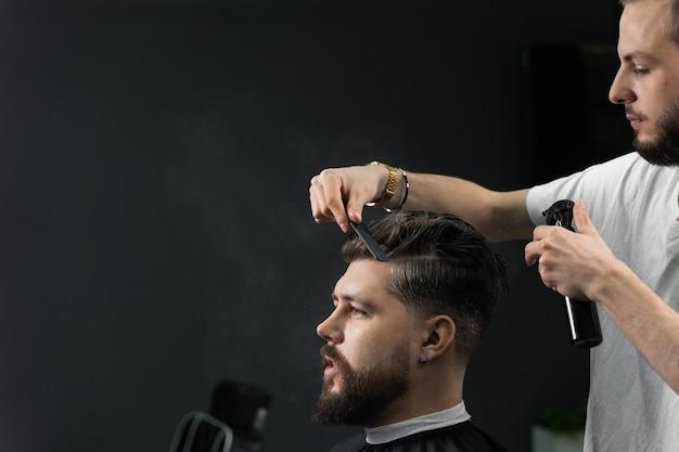 Low fade machine haarschnitt für gutaussehenden bärtigen mann im friseursalon. friseur mit schreckensschlössern, die frisur mit einem glatten übergang machen.