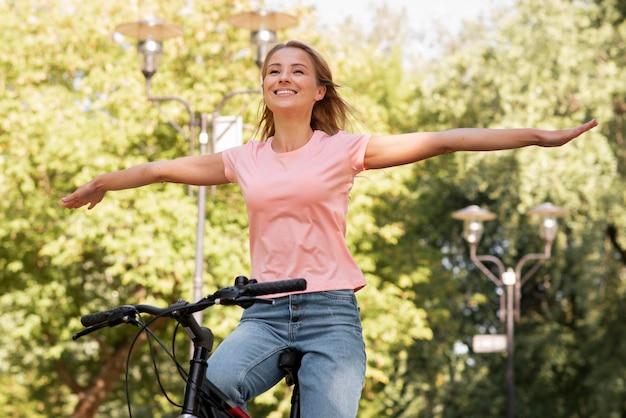 Low view frau reitet ohne das fahrrad mit den händen zu halten
