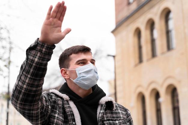 Low view mann trägt maske mit hand winken