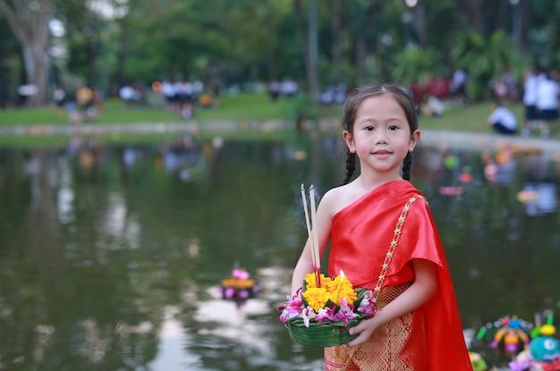 Loy krathong festival, asiatisches kindermädchen im thailändischen trachtenkleid