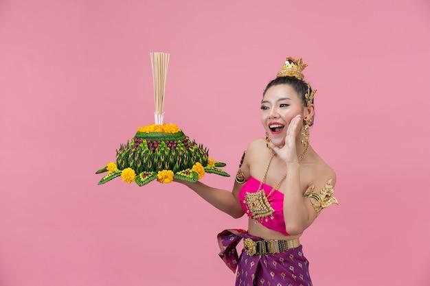 Loy krathong festival. frau im thailändischen traditionellen outfit hält dekorierten auftrieb