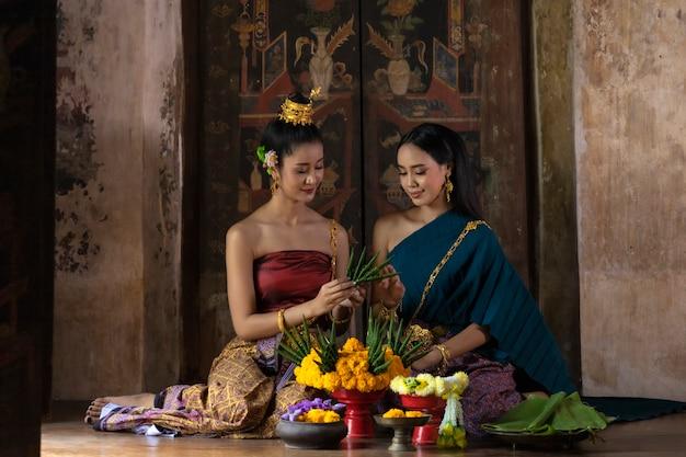 Loy krathong festival thailand. asiatinnen sind loy krathong auf einem fluss in der nacht.