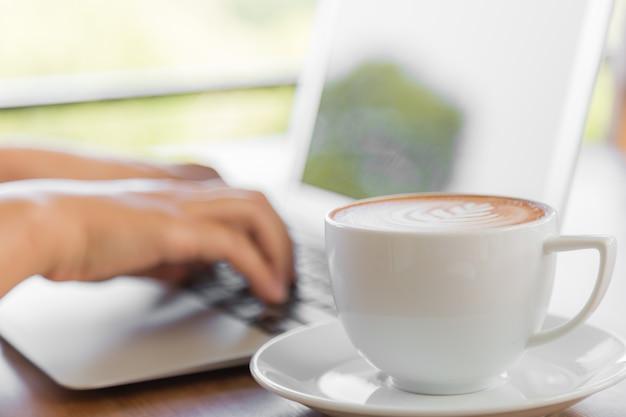Lperson arbeitet an einem laptop mit einer tasse kaffee neben