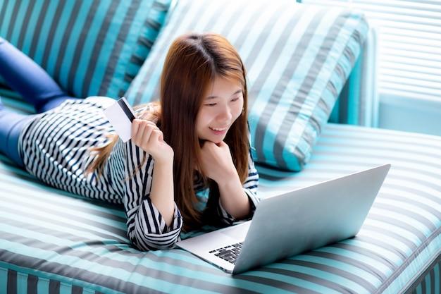 Lügenbenutzer kreditkarte der schönen asiatischen frau mit laptop