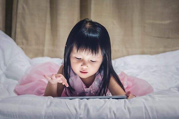 Lügenstablette des kleinen mädchens auf bett nachts unter verwendung des internets, das vdo oder spielspiel aufpasst
