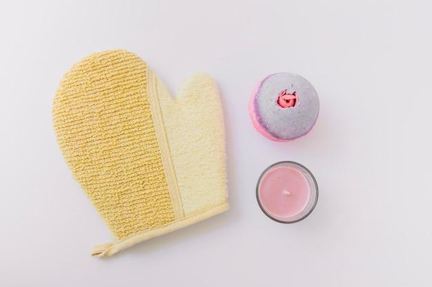 Luffa-handschuh; badebombe und kerze auf weißem hintergrund