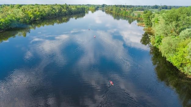 Luft draufsicht der leute kajakfahren, mann, der im kajak auf flusskanutour paddelt, spaß, aktives wochenende und urlaub, wassersport im freien und naturkonzept hat