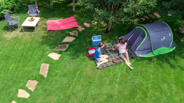Luft draufsicht des campingplatzes von oben, mutter und tochter, die spaß, zelt und campingausrüstung unter baum, familienurlaub im camp im freienkonzept haben