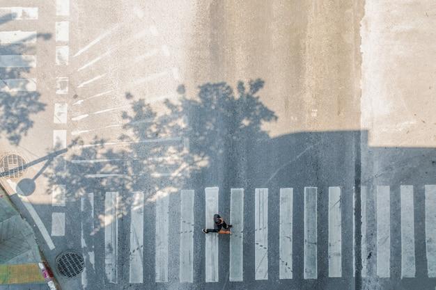Luft draufsicht des mannes gehen auf straße in der stadt über fußgängerüberweg verkehrsstraße.