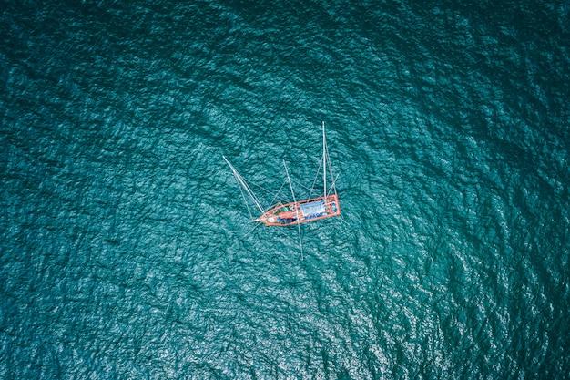 Luft-draufsicht-fischerboot auf dem grünen meer
