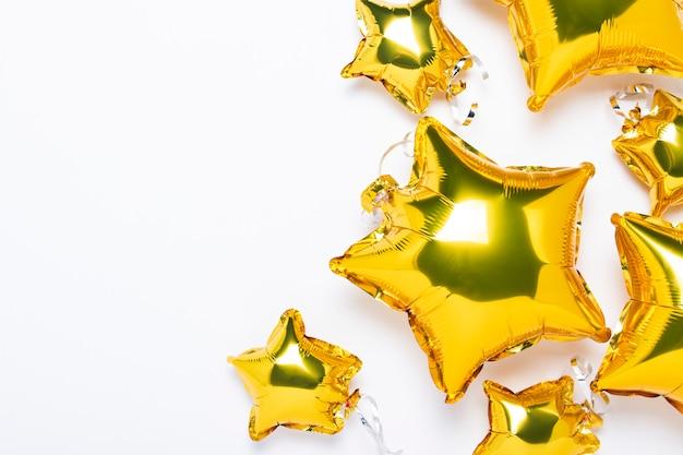 Luft goldene luftballons sternform und süßigkeiten auf einem weißen raum. konzept für urlaub, party, fotozone, dekoration