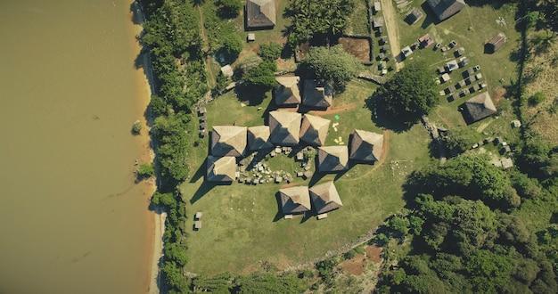 Luft oben tropische landschaft mit kunstvoll überdachten häuschen, häuser des traditionellen dorfes kampung tarung, sumba island, indonesien