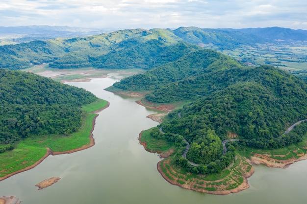 Luft über ansicht grüner bergwald und dammreservoirfluss in der regenzeit und kurvige straße auf dem hügel, der landschaft verbindet