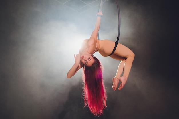 Luftakrobat im ring. ein junges mädchen führt die akrobatischen elemente im luftring aus.